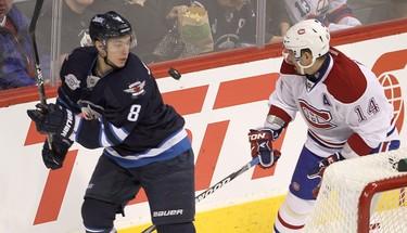 Winnipeg Jets center Alexander Burmistrov (l) and Montreal Canadiens center Tomas Plekanec chase the puck during NHL hockey in Winnipeg Thursday, December 22, 2011. BRIAN DONOGH/WINNIPEG SUN/QMI AGENCY