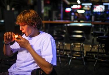 Russell Diercks smokes marijuana inside of Frankie Sports Bar and Grill in Olympia, Washington on December 9, 2012. (REUTERS/Nick Adams)