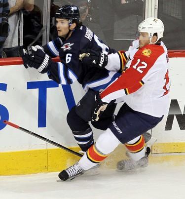 Winnipeg Jets defenceman Ron Hainsey (l) checks Florida Panthers right winger Jack Skille during NHL hockey in Winnipeg Thursday, March 01, 2012. BRIAN DONOGH/WINNIPEG SUN/QMI AGENCY