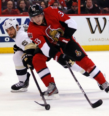 Pittsburgh Penguins' Deryk Engelland (5) tries to knock the puck away from Ottawa Senators' Jakob Silfverberg (33) during the third period of NHL hockey action at Scotiabank Place in Kanata, Sunday Jan. 27, 2013.  Darren Brown/Ottawa Sun/QMI Agency)