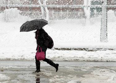 A woman walks along Preston St. in Ottawa's Little Italy  after a winter storm dumped up to 25 cms of wet snow over night Thursday, Feb. 28, 2013.  Darren Brown/Ottawa Sun/QMI Agency