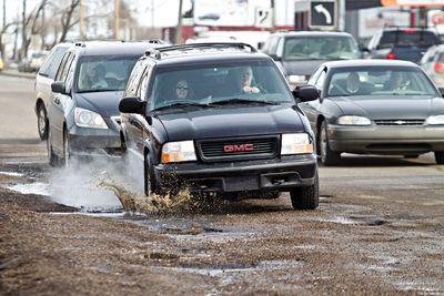 Vehicles navigate potholes on 63 Avenue and 99 Street in Edmonton, Alta., on Saturday, March 30, 2013. Codie McLachlan/Edmonton Sun/QMI Agency