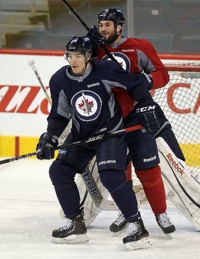 Winnipeg Jets defenceman Zach Redmond (l) blocks right winger Anthony Peluso during practice in Winnipeg, Man. Sunday April 14, 2013. BRIAN DONOGH/WINNIPEG SUN/QMI AGENCY