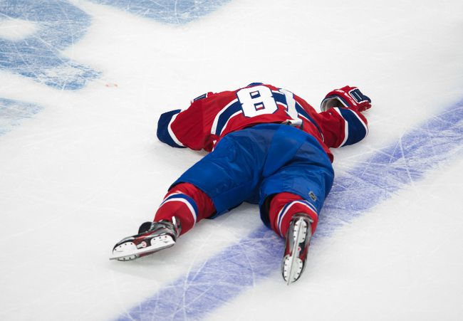 Canadiens forward Lars Eller lies on the ice after receiving a hit from Senators forward Eric Gryba. (Ben Pelosse/QMI Agency)