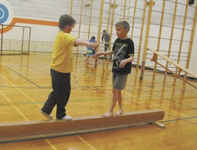 Wyatt Lange and Jaren Hermann, Grade 4 students, approach each other on a balance beam in gymnastics.