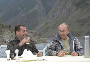 Russia's President Vladimir Putin (R) and Prime Minister Dmitry Medvedev drink on a boat in the Siberian Federal District July 20, 2013. REUTERS/Alexander Astafyev/RIA Novosti/Pool