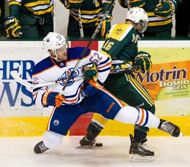 Edmonton Oilers rookie Austin Fyten gets hit by Golden Bears Sean Ringrose during first period hockey action at Clare Drake Arena in Edmonton, Alta. on Tuesday, Sep. 10, 2013.  Amber Bracken/Edmonton Sun/QMI Agency