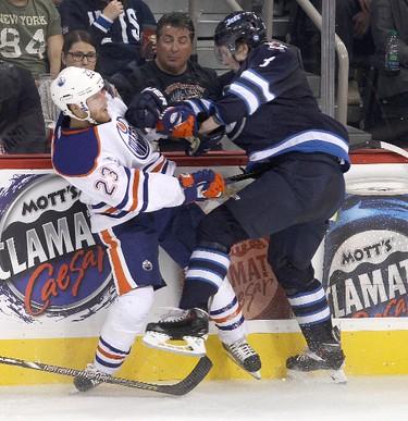 Edmonton Oilers left winger Linus Omark (l) is taken out of play by Winnipeg Jets defenceman Jacob Trouba during NHL hockey in Winnipeg, Man. Tuesday, September 17, 2013. BRIAN DONOGH/WINNIPEG SUN/QMI AGENCY