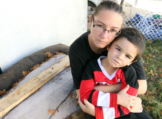 "Tammy Jackson hugs her son Joshua near where their badly beaten cat ""Tigger"" was found in their back yard in Winnipeg, Man. Sunday October 13, 2013.  BRIAN DONOGH/WINNIPEG SUN/QMI AGENCY"