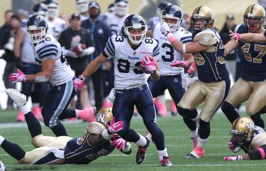 Toronto Argonauts WR Julian Feoli-Gudino is tripped up by Winnipeg Blue Bombers Carl Volny on a kick return during CFL action at Investors Group Field in Winnipeg, Man., on Sat., Oct. 19, 2013. Kevin King/Winnipeg Sun/QMI Agency