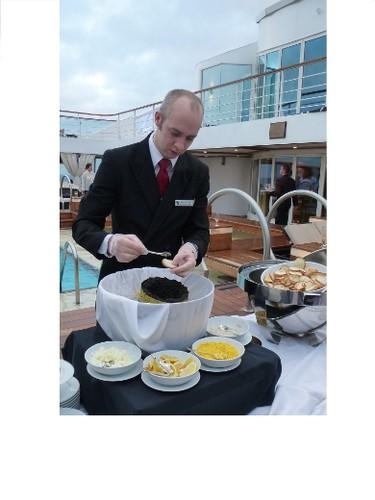 Darren Beckett, assistant maitre d'hotel, spreads serves caviar during an epicurean event aboard the Seabourn Sojourn. ROBIN ROBINSON/TORONTO SUN