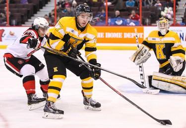 Kingston Frontenacs Warren Steele (77) moves the puck away from Ottawa 67's Joseph Blandisi as netminder Matt Mahalak follows the play during OHL hockey action at the Canadian Tire Centre in Ottawa. December 20, 2013. Errol McGihon/Ottawa Sun/QMI Agency