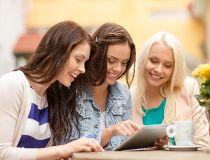 Three beautiful woman looking at a tablet computer