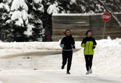 Women run along snow-covered roads in Ottawa on Monday December 23, 2013. Darren Brown/Ottawa Sun/QMI Agency