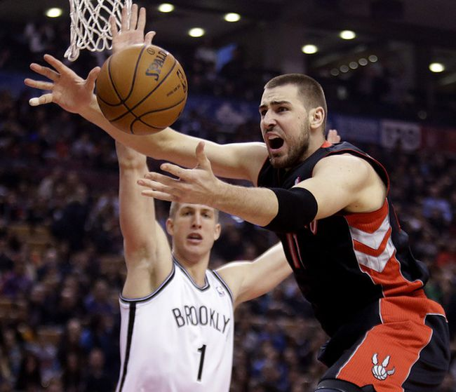 Raptor Jonas Valanciunas tries to handle the ball against Brooklyn Nets' Mason Plumlee on Jan. 11. (Craig Robertson/Toronto Sun/QMI Agency)