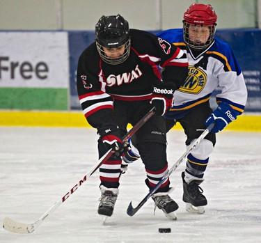 Whitemud West Thunderkings' Steele Bailey (in white) pursues SWAT Stars' Rishi Mahant (in black) during Quikcard Edmonton Minor Hockey Week action at Mill Woods Recreation Centre in Edmonton, Alta., on Wednesday, Jan. 15, 2014. Codie McLachlan/Edmonton Sun/QMI Agency