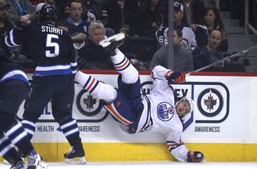 Winnipeg Jets defenceman Mark Stuart (left) sends Edmonton Oilers forward Ryan Jones flying with a bodycheck during NHL action at MTS Centre in Winnipeg, Man. on Sat., Jan. 18, 2014. Kevin King/Winnipeg Sun/QMI Agency