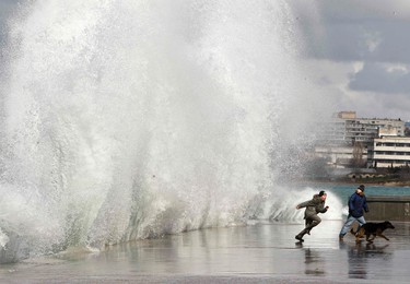 Children run from a wave on the promenade during a storm in Sevastopol, Ukraine, March 3, 2012. (REUTERS/Gleb Garanich)