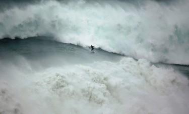 Big-wave surfer Garrett McNamara of the U.S. drops in on a large wave at Praia do Norte, in Nazare, Portugal, November 1, 2013. (REUTERS/Rafael Marchante)
