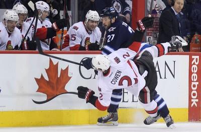 Winnipeg Jets forward Eric Tangradi (27) dumps Ottawa Senators defenceman Jared Cowen with a bodycheck during NHL action at MTS Centre in Winnipeg, Man., on Sat., March 8, 2014. Kevin King/Winnipeg Sun/QMI Agency