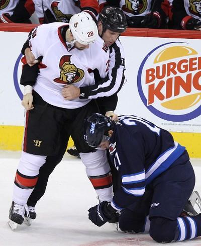 Ottawa Senators forward Matt Kassian (left) is called for roughing Winnipeg Jets forward Eric Tangradi during NHL action at MTS Centre in Winnipeg, Man., on Sat., March 8, 2014. Tangradi injured Eric Condra with a hit earlier in the second period. Kevin King/Winnipeg Sun/QMI Agency