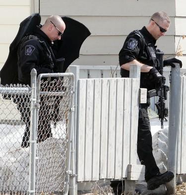 Members of the Winnipeg Police tactical unit exit a house following a raid at 707 Selkirk Avenue in Winnipeg, Man. Sunday April 06, 2014. Brian Donogh/Winnipeg Sun/QMI Agency