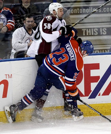 Edmonton Oilers Matt Hendricks (23) checks battles the Colorado Avalanche's Patrick Bordeleau (58) during first period NHL action at Rexall Place in Edmonton Alberta, Alta., on Tuesday April 8, 2014. David Bloom/Edmonton Sun/QMI Agency