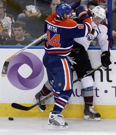 Edmonton Oilers Ryan Smyth (94) checks the Colorado Avalanche's Tyson Barrie (4) during third period NHL action at Rexall Place in Edmonton Alberta, Alta., on Tuesday April 8, 2014. David Bloom/Edmonton Sun/QMI Agency