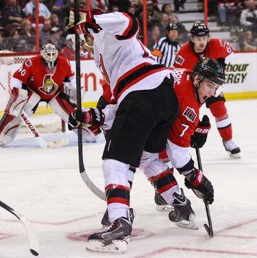 Ottawa Senators' Kyle Turris battles with New Jersey Devils' Travis Zajac during NHL hockey action at the Canadian Tire Centre in Ottawa, Ontario on Thursday April 10, 2014. Errol McGihon/Ottawa Sun/QMI Agency