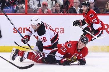 Ottawa Senators' Chris Neil is taken to the ice by New Jersey Devils' Steve Bernier as Sen Mike Hoffman follows the play during NHL hockey action at the Canadian Tire Centre in Ottawa, Ontario on Thursday April 10, 2014. Errol McGihon/Ottawa Sun/QMI Agency