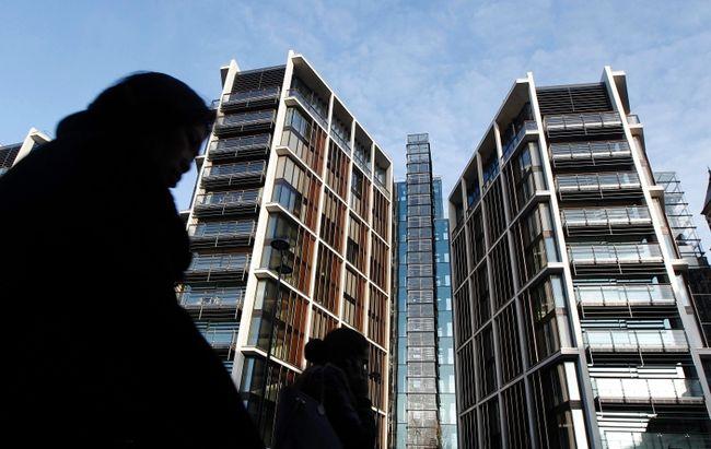 Pedestrians pass new development One Hyde Park in London Jan. 19, 2011.  REUTERS/Luke MacGregor
