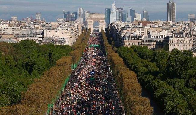 Racers run down the Champs Elysees below the Arc de Triomphe at the start of the 38th Paris Marathon April 6, 2014.  GONZALO FUENTES/REUTERS