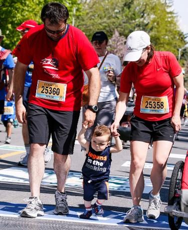 Taylor Douglas and Amanda Douglas cross the finish line with their young son in the Ottawa 2K on Saturday  May 24, 2014. Errol McGihon/Ottawa Sun/QMI Agency