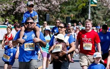 A family approach the finish line in the Ottawa 2K on Saturday May 24, 2014. Errol McGihon/Ottawa Sun/QMI Agency