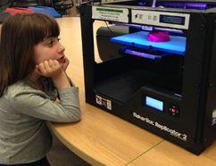 Aphrodite Thomaidis, 4, plays with the 3D printer at the Pickering Public Library. (Irene Thomaidis/QMI Agency)