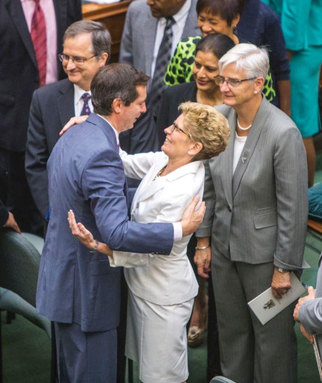 Ontario Premier Kathleen Wynne  embraces former premier Dalton McGuinty in the legislature after the throne speech on July 3, 2014. (Ernest Doroszuk/Toronto Sun)