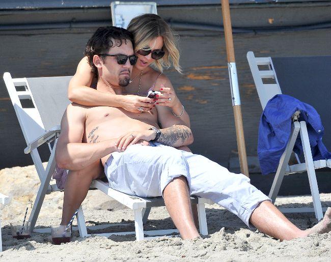 Kaley Cuoco and her husband Ryan Sweeting cuddle on the beach in Malibu in May 2014. (WENN.com)