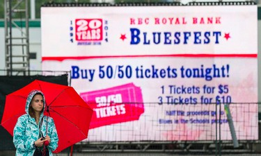 Jenna MacCaull waits in the rain for shows to start at Bluesfest on Tuesday July 8, 2014. Errol McGihon/Ottawa Sun/QMI Agency