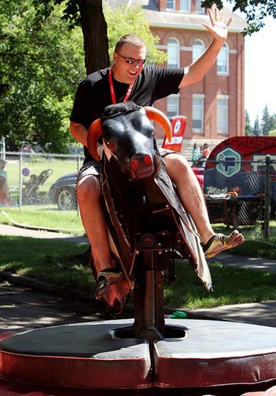 Darwin Holm rides a mechanical bull during the 2nd annual Ronald McDonald House Northern Alberta Block Party, near 7726 - 107 St., in Edmonton Alta., on Sunday July 27, 2014. David Bloom/Edmonton Sun/ QMI Agency