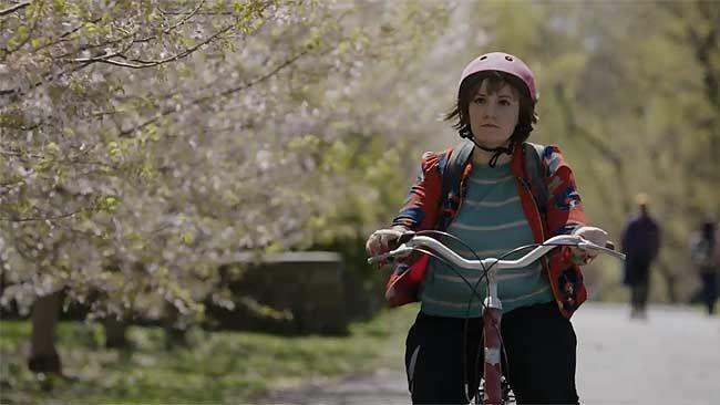 """Lena Dunham's Hannah rides a bike down a shady, beautiful path in the trailer for season four of """"Girls"""". (Screen grab)"""
