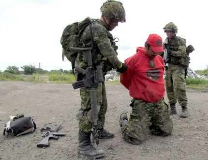MCpl. Leslie Anderson of Kasabonika kneels as soldiers take him prisoner during a military exercise.
