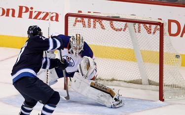 Winnipeg Jets forward TJ Galiardi (l) scores a goal against Edmonton Oilers goalie Laurent Brossoit during NHL hockey in Winnipeg, Man. Wednesday, September 24, 2014. Brian Donogh/QMI Agency