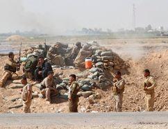 Volunteers with Kurdish peshmerga forces clash with Islamic State militants in the town of Daquq, south of Kirkuk, September 30, 2014. (REUTERS/Ako Rasheed)