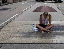 A protester sits under an umbrella as he attends a rally along a main street at Hong Kong's shopping district Tsim Sha Tsui October 1, 2014. REUTERS/Tyrone Siu