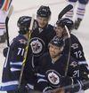 Winnipeg Jets forward TJ Galiardi cerebrates a goal against the Edmonton Oilers with teammates Julian Melchiori, Adam Lowry and  Scott Kosmachuk at the MTS Centre on September 24, 2014. (Brian Donogh/Winnipeg Sun/QMI Agency)