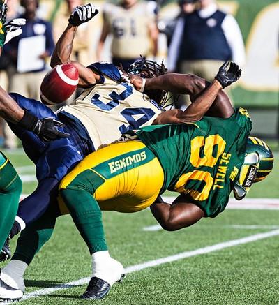Edmonton's Almondo Sewell (90) tackles Winnipeg's Paris Cotton (34) during the Edmonton Eskimos' CFL football game against the Winnipeg Blue Bombers at Commonwealth Stadium in Edmonton, Alta., on Monday, Oct. 13, 2014. Codie McLachlan/Edmonton Sun/QMI Agency