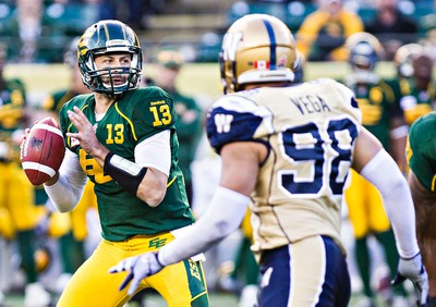 Edmonton's quarterback Mike Reilly (13) is watched by Winnipeg's Jason Vega (98) during the Edmonton Eskimos' CFL football game against the Winnipeg Blue Bombers at Commonwealth Stadium in Edmonton, Alta., on Monday, Oct. 13, 2014. The Eskimos won 41-9. Codie McLachlan/Edmonton Sun/QMI Agency