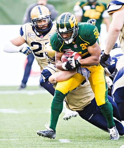 Edmonton's John White (30) is tackled during the Edmonton Eskimos' CFL football game against the Winnipeg Blue Bombers at Commonwealth Stadium in Edmonton, Alta., on Monday, Oct. 13, 2014. The Eskimos won 41-9. Codie McLachlan/Edmonton Sun/QMI Agency