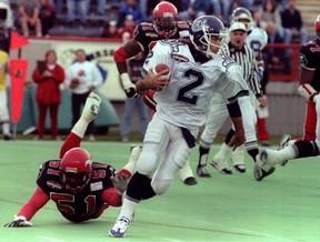 Toronto Argonauts quarterback Doug Flutie eludes the tackle of Calgary Stampeders linebacker Alondra Johnson in the second quarter of their CFL game on October 14, 1996. (QMI Agency)