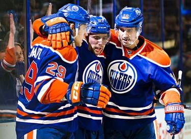 Edmonton's Leon Draisaitl (29), David Perron (57) and Teddy Purcell (16) celebrate Draisaitl's goal during the Edmonton Oilers' NHL hockey game against the Ottawa Senators at Rexall Place in Edmonton, Alta., on Thursday, Nov. 13, 2014. Codie McLachlan/Edmonton Sun/QMI Agency